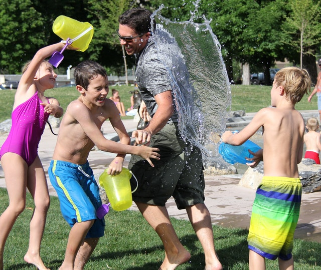 Kids in bathing suits use buckets to splash water on each other.