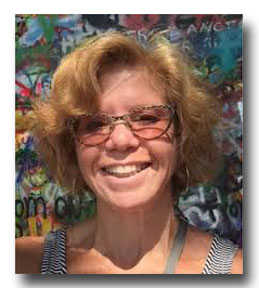 Marilyn Stein is a smiling woman with glasses and wavy light-brown hair