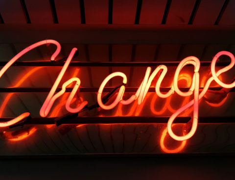 The word change in orange neon against a dark background