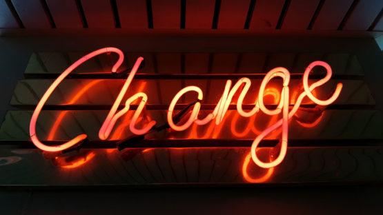 The word change in orange neon against a dark background