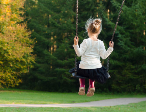 A young girl of around five sits on a swing- we see her from the back.