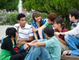 A group of seven teens relax outside of school.