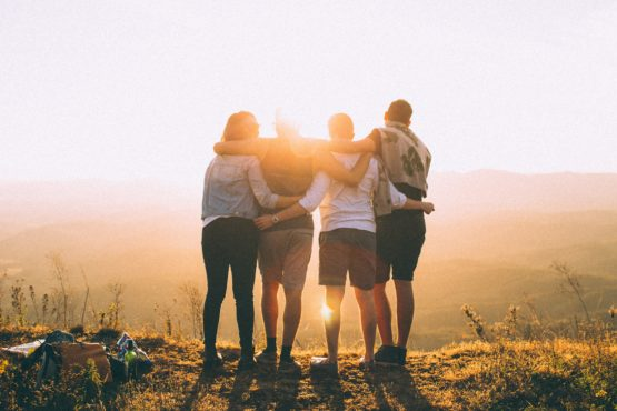 Four people look out over a valley in the setting (or rising?) sun