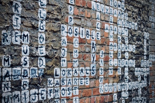 "A mural on the side of a building has letters and words arranged like a crossword puzzle. In the center we see the word ""possible."""