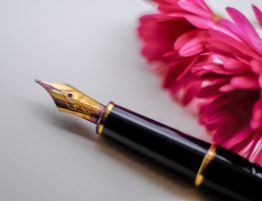 A close up of an ink pen and a pink flower
