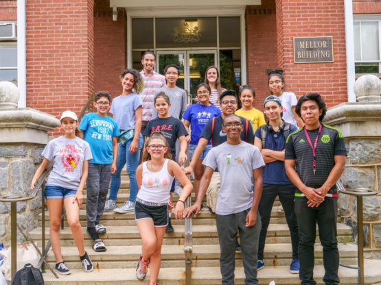 A group of middle-school students stand on the steps of Thaddeus Stevens College