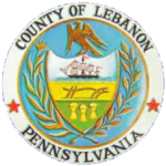 The seal of Lebanon County, PA is a circle with a coat of arms inside, depicting 3 rural scenes. An eagle perches atop the coat of arms.