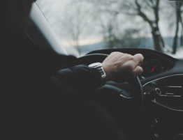 Closeup of a man's hand on a steering wheel