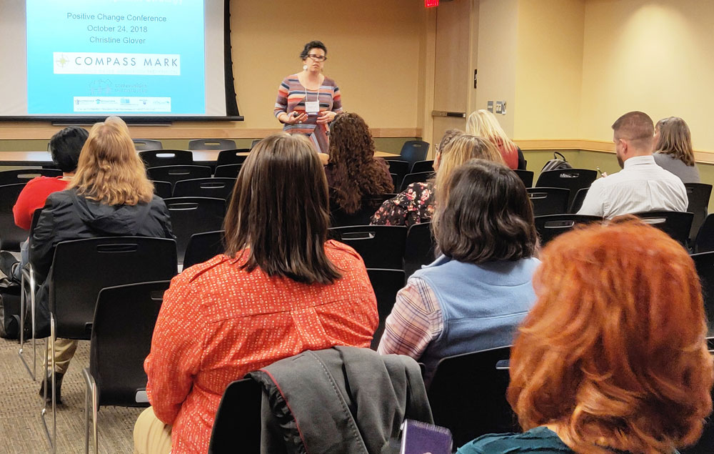 A woman presents to a group of people at a conference in front of a projection screen.