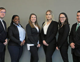 Six college students in business attire pose.
