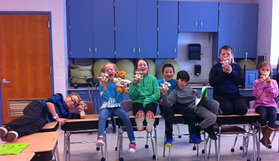 Seven elementary-aged students sit on desks in their classroom, holding stuffed bears and grinning.