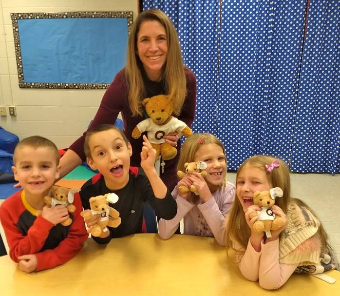 A young teacher and 4 smiling elementary-aged kids smile and hold up stuffed teddy bears