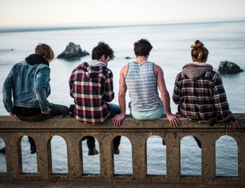 We see the backs of 4 teens sitting on the edge of a bridge- water in the background. It's gray out, and they seem quiet.