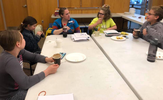 Five people work around a table while having a snack.