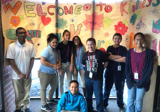 A group of middle school students pose in front of a homemade banner promoting kindness