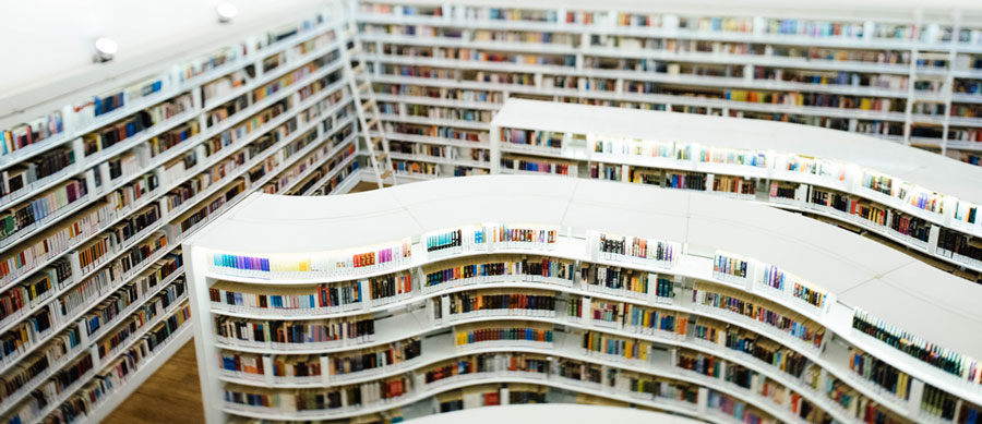 A modern library has curving, white shelves packed with colorful books. We want to go there!