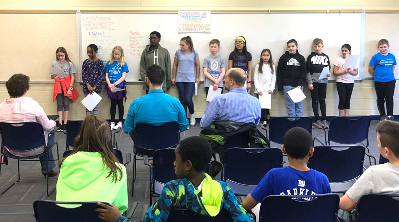 A group of middle school students present an idea to a group of adults. The kids stand at the front of the room, and we see the backs of the adults, seated.