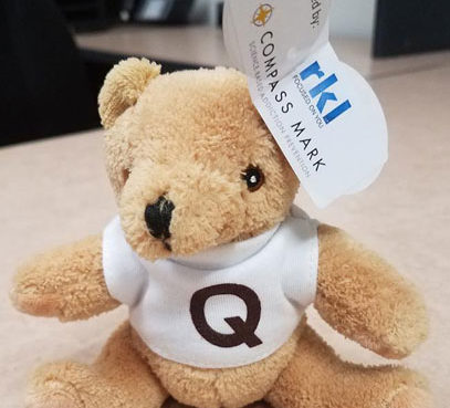 "A teddy bear wears a white shirt with a ""Q"" on it, as well as a tag that reads, ""Sponsored by RKL"""