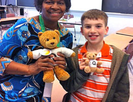 In a classroom, a woman and elementary-aged student pose with a stuffed bear.