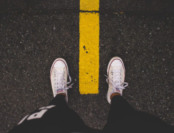 We see 2 feet in white sneakers, one on either side of a yellow dotted line on a roadway.