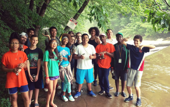 A group of tweens and teens pose in summer clothes in a wooded stream