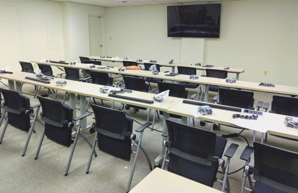 An empty training center contains rows of tables with chairs and a projection monitor