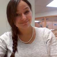 A young woman with a dark braid and business attire smiles informally