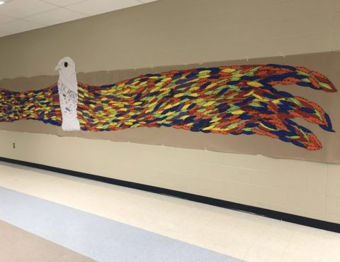 A coloful eagle stretches along the hall of a middle school. It's feathers are made up of indivual cut-outs with inspirational words written by the kids.