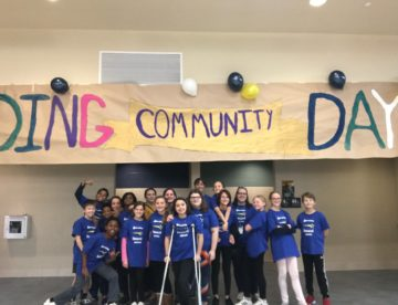 "A group of middle school students in matching shirts stand in front of a huge banner reading ""Building Community Day"""