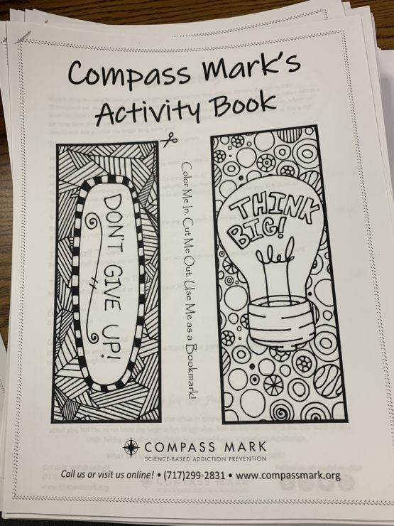 """A black and white drawing with bookmarks to color and the headline """"Compass Mark's Activity Book"""""""