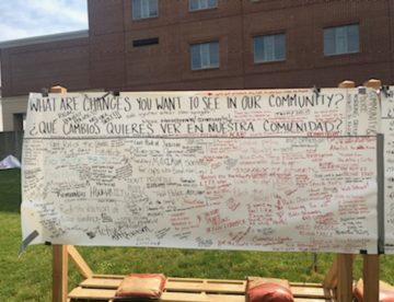 """A photo of a community board in downtown Lancaster, PA asks everyone in English & Spanish, """"what are changes you want to see in our community?"""" there are many replies, too small to read"""