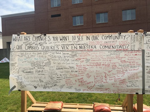 "A photo of a community board in downtown Lancaster, PA asks everyone in English & Spanish, ""what are changes you want to see in our community?"" there are many replies, too small to read"