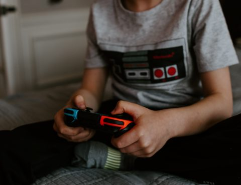 We see the torso and legs of a young person, possibly male or gender-neutral, sitting on a bed and playing video games.