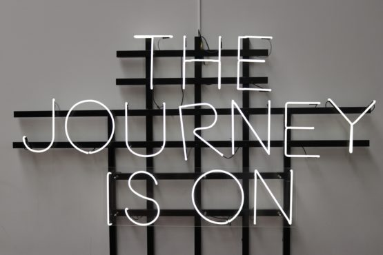 A neon sign is fixed to a white wall. The letters are white, and read: The Journey is On.