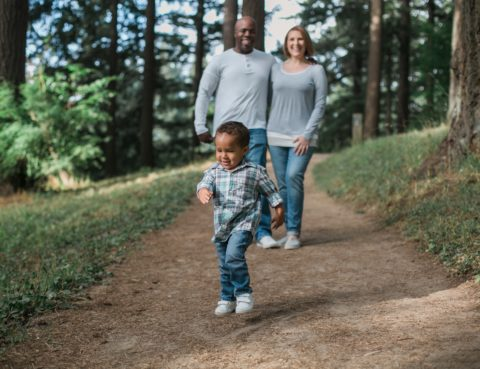 A path comes out of a forest, and we see a toddler first, and behind him, mom and dad, arms around each other, smiling.