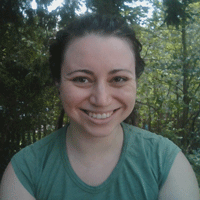 Close up of a young woman smiling in a casual shirt with green trees behind her.