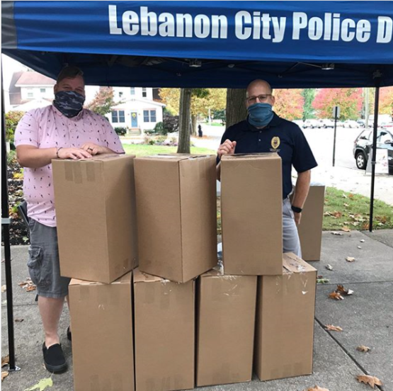 Two men stand outside under a tent in back of cardboard boxes. They are wearing masks.
