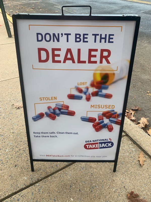 "A sign outside on a sidewalk says ""Don't Be the Dealer"" with images of prescription medications."