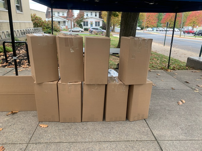 10 carboard boxes are stacked on a sidewalk
