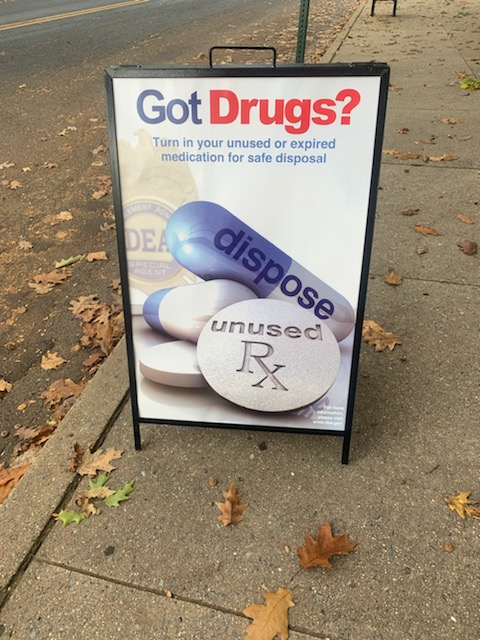 "An outside sign on a sidewalk says, ""Got Drugs?"" with tablets and pills."