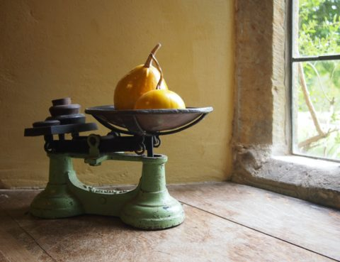 On an old wooden table we see an old-fashioned balance scale, with pears and weights in the pans. It's near a window.