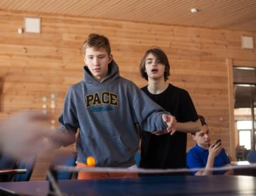 Two teen boys are shown playing ping pong in a rustic hall.