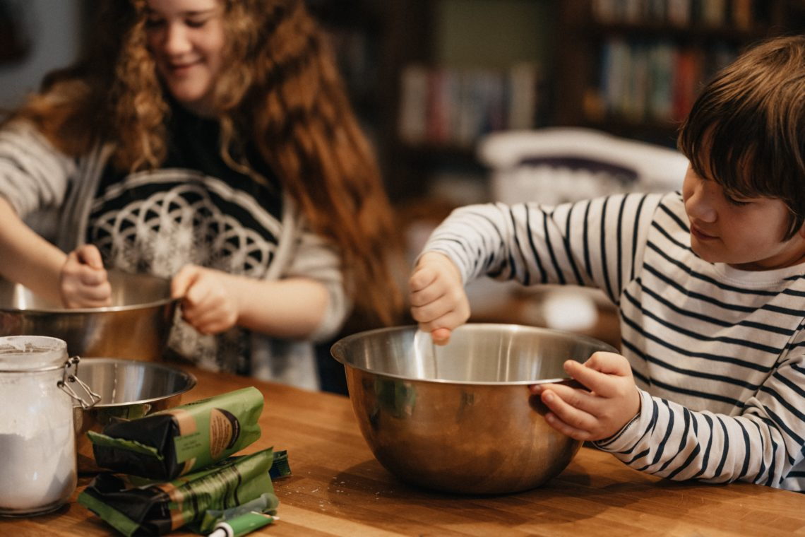 Teen and younger child mix things in bowls at a table- maybe they are making a meal?