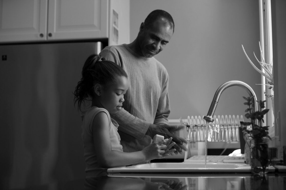 Father and daughter of 8 or 9 years stand at a kitchen sink washing dishes. He looks at her fondly.